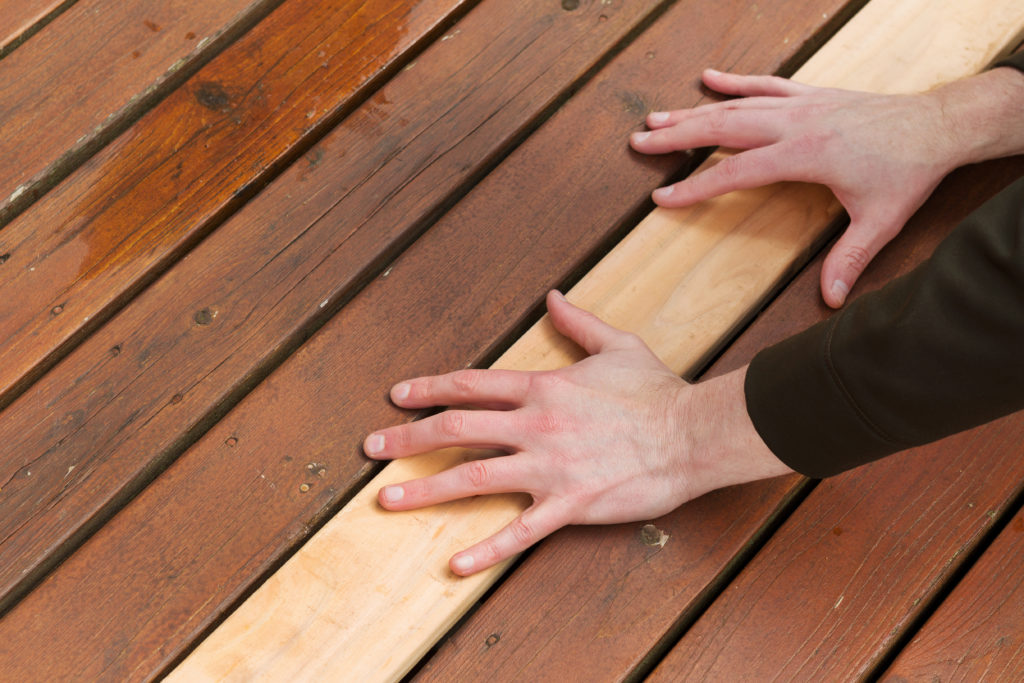 a brand new board on a deck lying amongst older boards with two hands on top holding it down is part of a carpentry repair